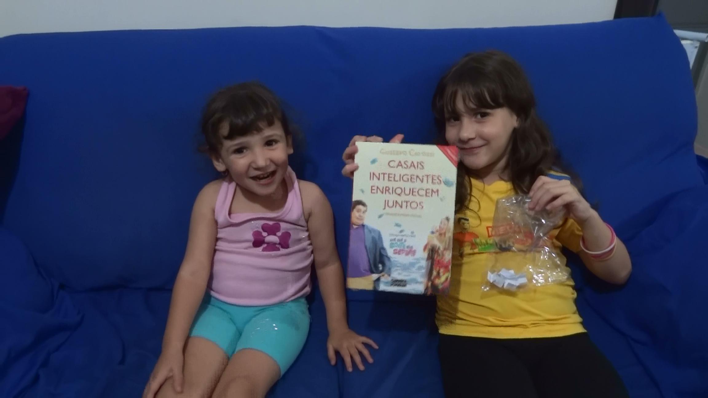 Amanda e Letícia mostrando o livro sorteado